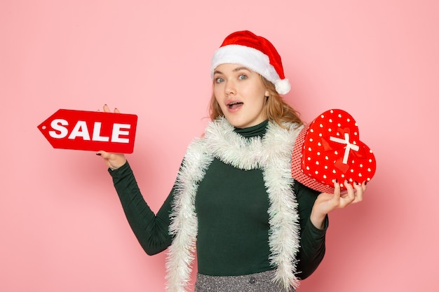 Front view young female holding red sale writing and present on pink wall christmas new year shopping emotions holiday