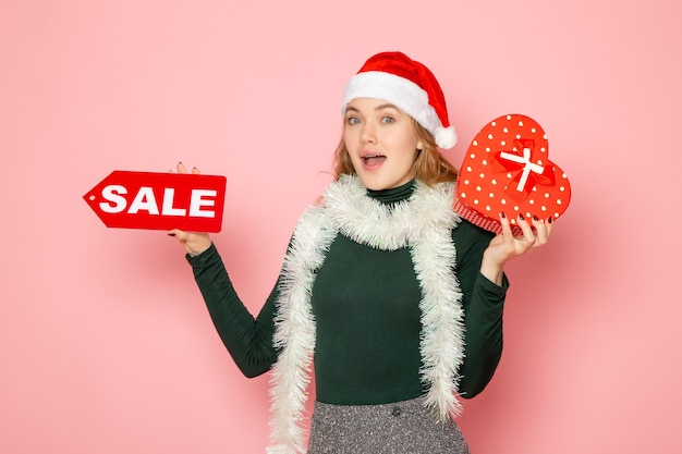 Front view young female holding red sale writing and present on pink wall new year shopping emotion holiday