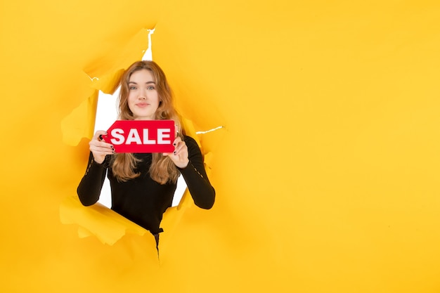 Giovane femmina di vista frontale che tiene la scrittura rossa di vendita sul muro strappato giallo