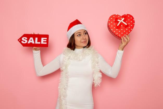 ピンクの壁の色の休日新年ファッション雪に販売執筆とプレゼントを保持している正面図若い女性