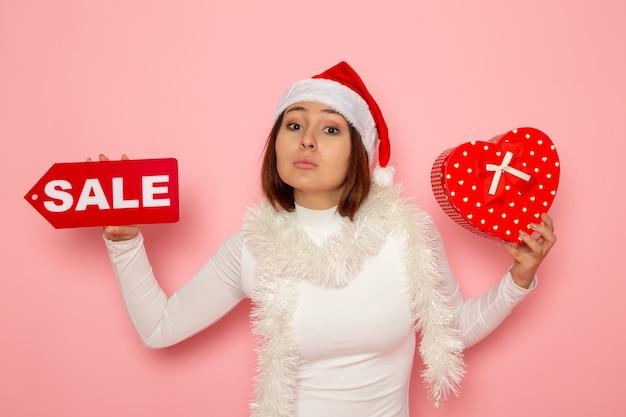 ピンクの壁の色の休日新年雪クリスマスに販売執筆とプレゼントを保持している正面図