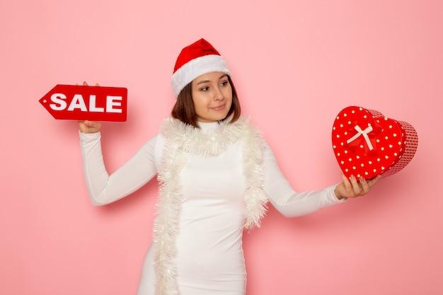 ピンクの壁の色の休日新年ファッション雪のクリスマスに販売執筆とプレゼントを保持している正面図若い女性