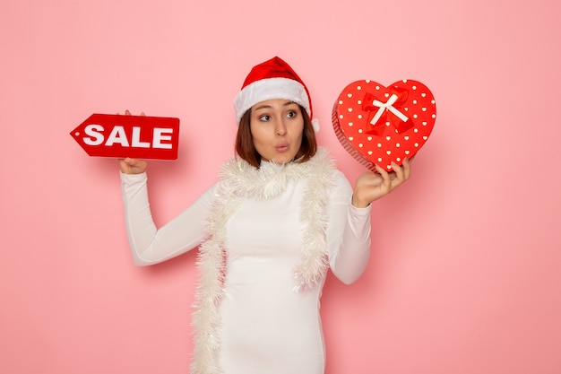 판매 쓰기를 들고 전면보기 젊은 여성 핑크 벽 휴가 새 해 패션 눈 크리스마스에 선물