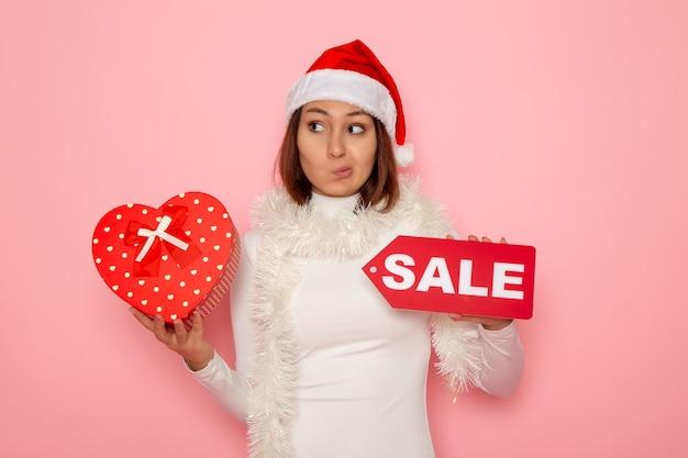 正面図若い女性が販売を保持し、ピンクの壁にプレゼントを書く雪クリスマス色休日新年ファッション