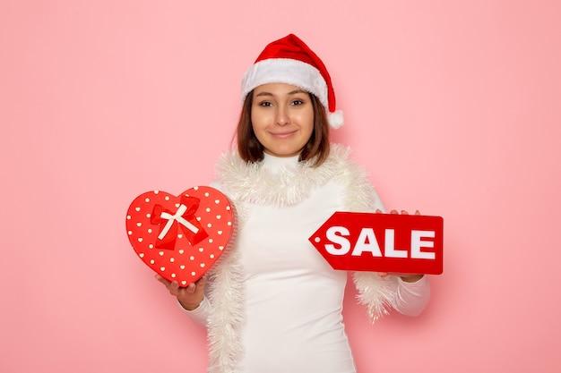Vista frontale giovane femmina azienda vendita scrittura e presente sulla parete rosa colore moda vacanza capodanno neve natale