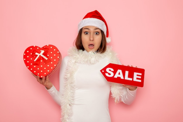 Vista frontale giovane donna azienda vendita scrittura e presente sulla parete rosa colore moda vacanze capodanno neve natale