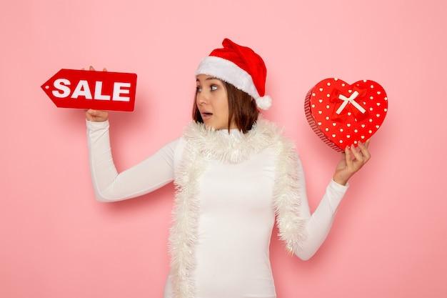 Vista frontale giovane femmina azienda vendita scrittura e presente sulla parete rosa colore vacanza capodanno moda neve natale