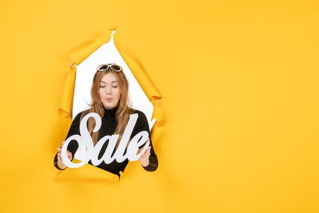 Vista frontale giovane donna che tiene la vendita scritta attraverso il buco della carta strappata nel muro