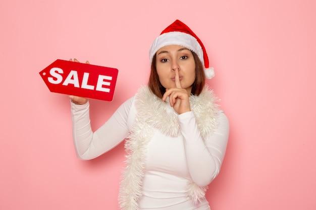 Figura scritta di vendita della tenuta della giovane femmina di vista frontale che chiede di tacere sulla neve di modo di festa del nuovo anno di natale di colore della parete rosa