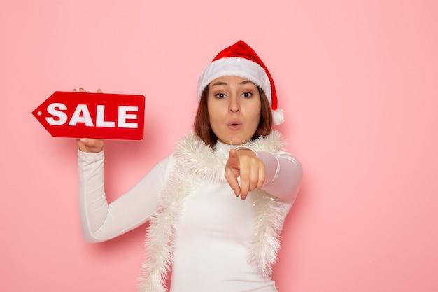 전면보기 젊은 여성 지주 판매 핑크 벽 색상 크리스마스 새해 휴일 패션 눈에 그림을 작성