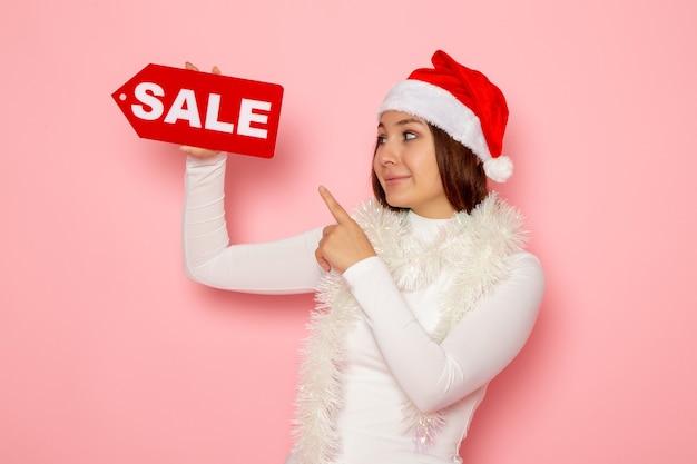 正面図ピンクの壁の色の雪のクリスマス新年の休日のファッションに販売書面による販売を保持している若い女性