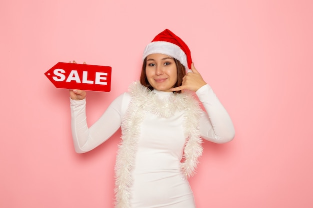 Front view young female holding sale written figure on pink wall color holidays new year fashion snow christmas