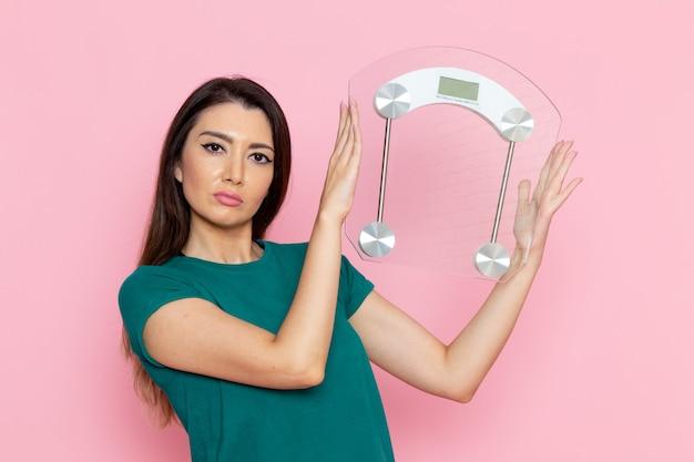 正面図ライトピンクの壁に体重計を保持している若い女性運動スポーツトレーニングアスリートウエストの美しさ