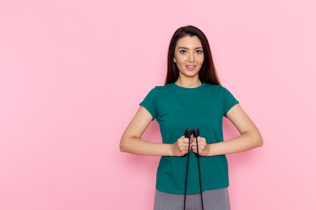 Вид спереди молодая женщина, держащая скакалку на розовой стене, спортивная тренировка, спортсменка, талия, красота