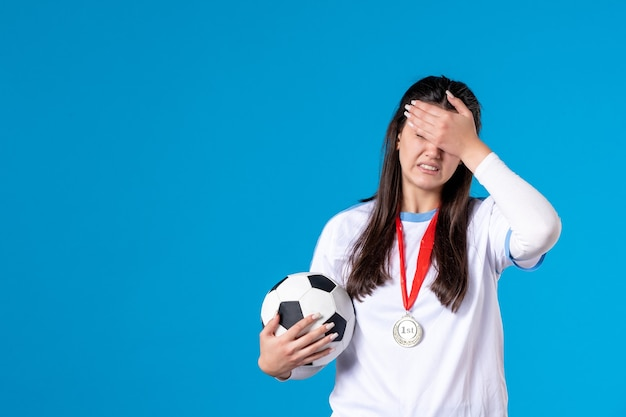 Front view young female holding soccer ball on blue wall