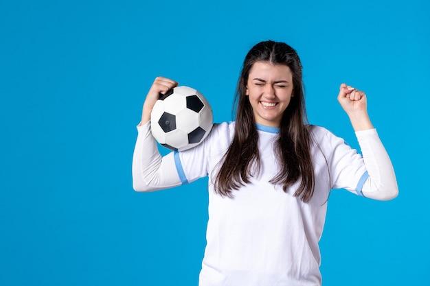 青い壁にサッカーボールを保持している若い女性の正面図