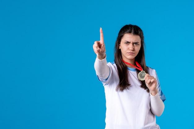 Вид спереди молодая женщина держит футбольный мяч на синей стене