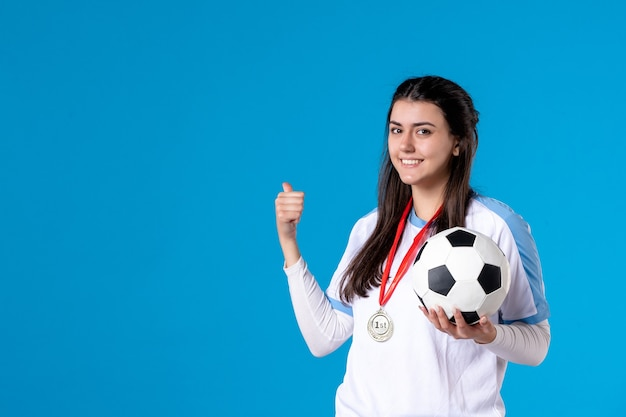Вид спереди молодая женщина, держащая футбольный мяч