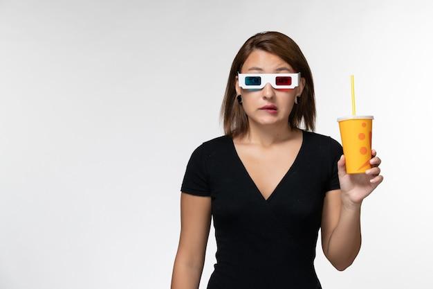 Vista frontale giovane femmina che tiene soda in occhiali da sole d su superficie bianca leggera