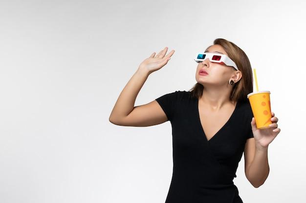 Vista frontale giovane femmina di soda in possesso di occhiali da sole d cercando sulla superficie bianca