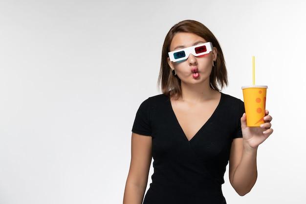 Vista frontale giovane femmina che tiene soda in d occhiali da sole e facendo facce buffe sulla superficie bianca