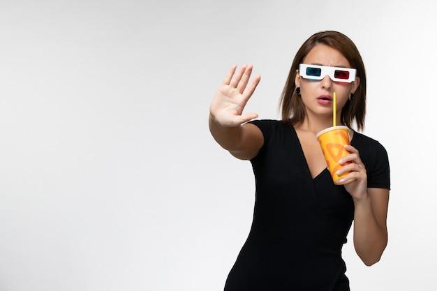 Soda femminile giovane della tenuta di vista frontale in occhiali da sole di d sullo scrittorio bianco