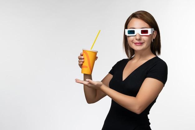 Soda femminile giovane della tenuta di vista frontale in occhiali da sole di d su superficie bianca