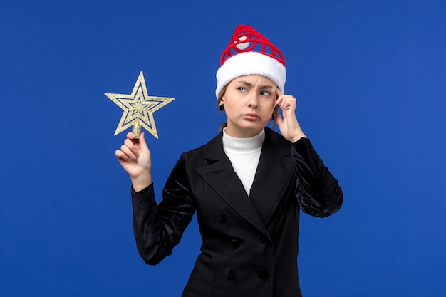 Front view young female holding star shaped decor on blue floor new year holiday woman