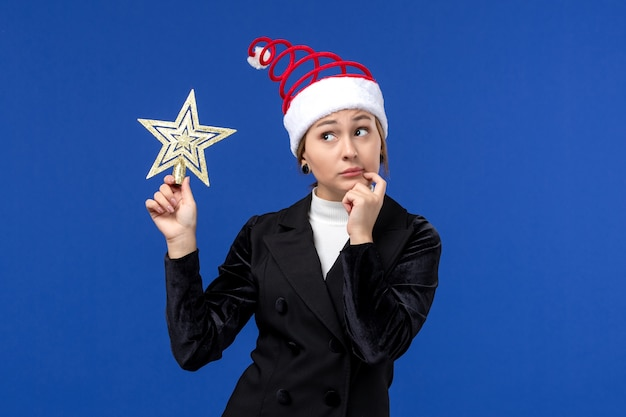 Front view young female holding star shaped decor on blue wall new year holidays woman