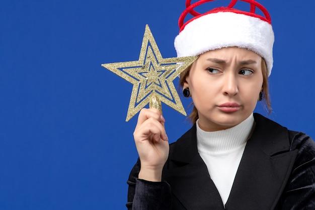 Giocattolo a forma di stella della giovane tenuta femminile di vista frontale sulla vigilia del nuovo anno di feste blu della parete