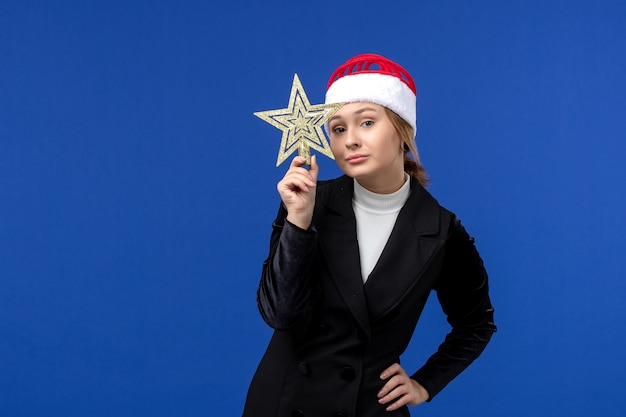 Front view young female holding star shaped toy on a blue wall new year woman holiday