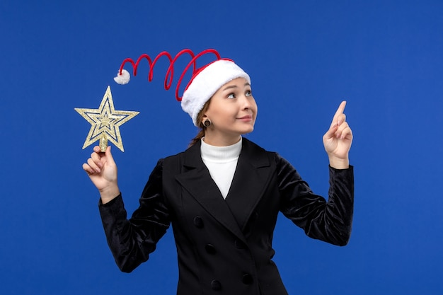 Front view young female holding star shaped toy on light blue background holiday woman new year