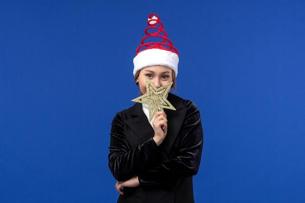 Вид спереди молодая женщина с игрушкой в форме звезды на синей стене новогодний праздник