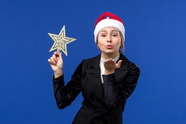 Вид спереди молодая женщина держит игрушку в форме звезды на синей стене новогодних праздников женщина