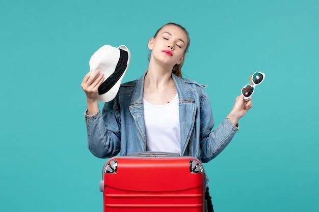 正面図水色の空間にサングラスと帽子を保持している若い女性
