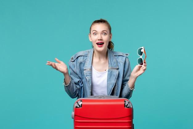 선글라스를 들고 밝은 파란색 공간에서 휴가를 준비하는 전면보기 젊은 여성 무료 사진