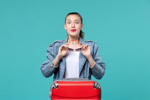 サングラスを保持し、青いスペースで休暇の準備をしている正面図若い女性