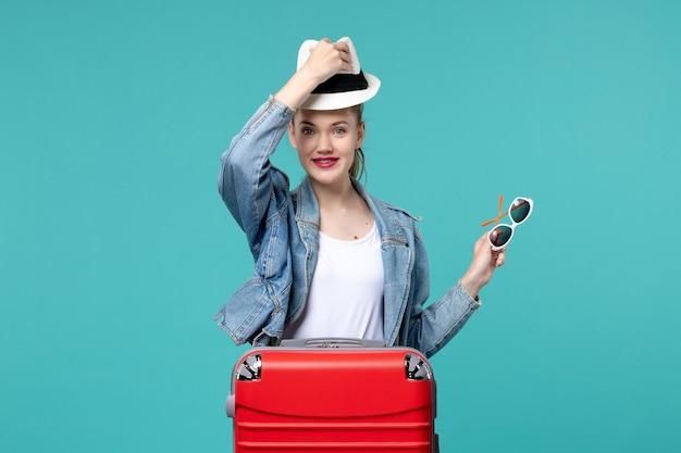 Вид спереди молодая женщина держит солнцезащитные очки и в шляпе на синем пространстве