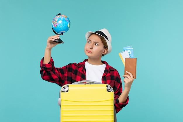 Вид спереди молодая женщина, держащая билеты и глобус на синем пространстве