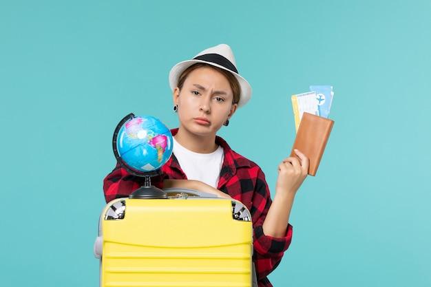 Giovane femmina di vista frontale che tiene i biglietti sullo spazio azzurro