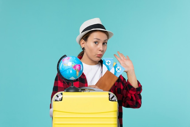 水色のスペースでチケットを保持している若い女性の正面図