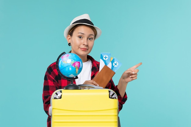 青い床の航海休暇旅行の女性の旅のチケットを保持している正面図若い女性