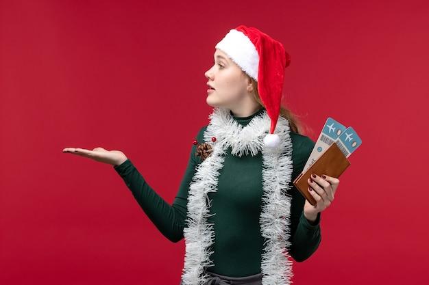 Вид спереди молодая женщина, держащая билеты на красном фоне