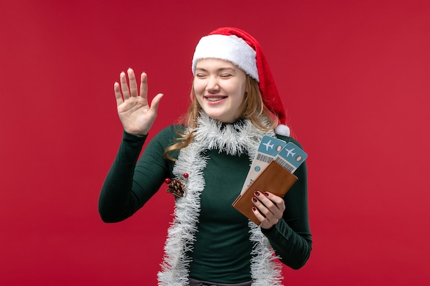 Front view young female holding tickets on a red background