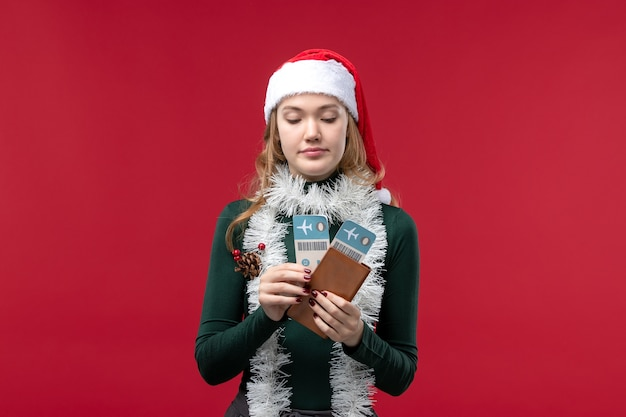 Front view young female holding tickets on red background