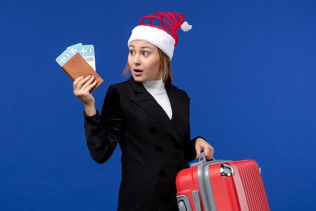 Giovane femmina di vista frontale che tiene i biglietti con la borsa sulle vacanze di vacanza della donna del fondo blu
