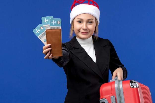 青い背景の飛行機の休日の休暇でバッグとチケットを保持している若い女性の正面図
