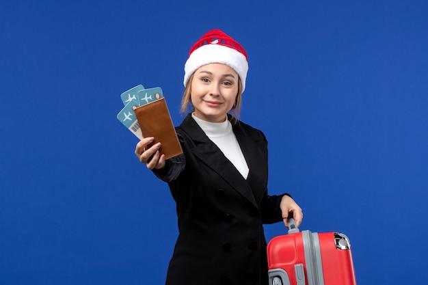 Вид спереди молодая женщина, держащая билеты с сумкой на синем столе, праздники, самолет, отдых