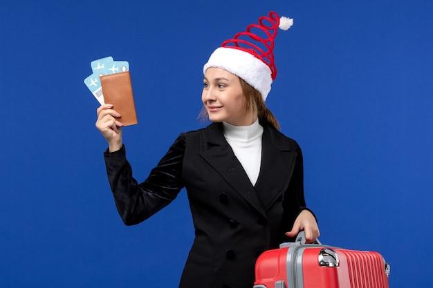 Вид спереди молодая женщина, держащая билеты с сумкой на синем столе, праздник отпуска женщины