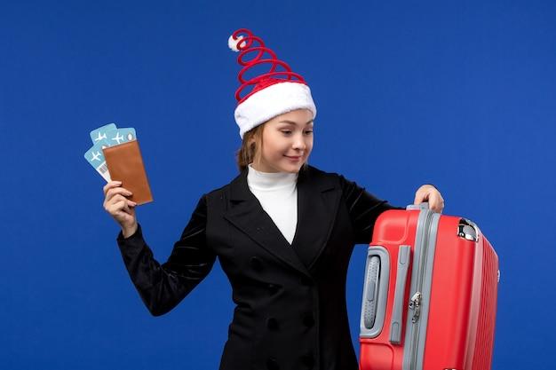 Вид спереди молодая женщина, держащая билеты с сумкой на синем столе, женщина в отпуске